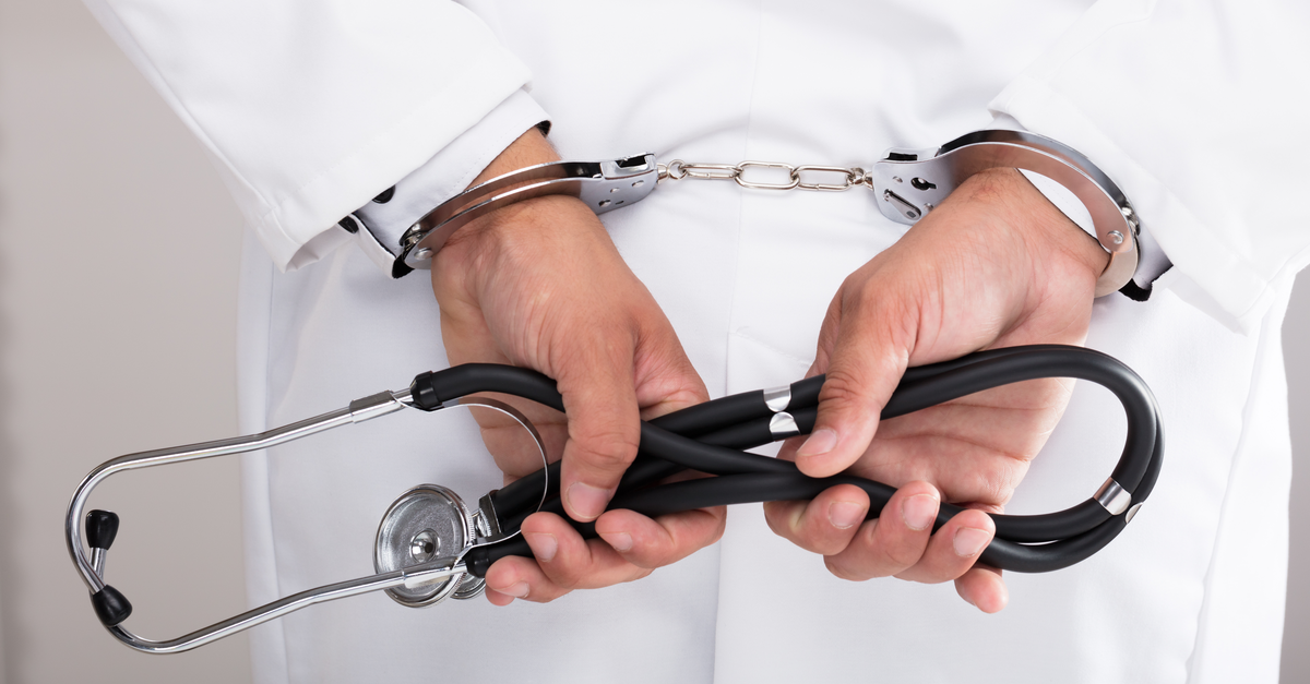 doctors hand handcuff holding stethoscope behind