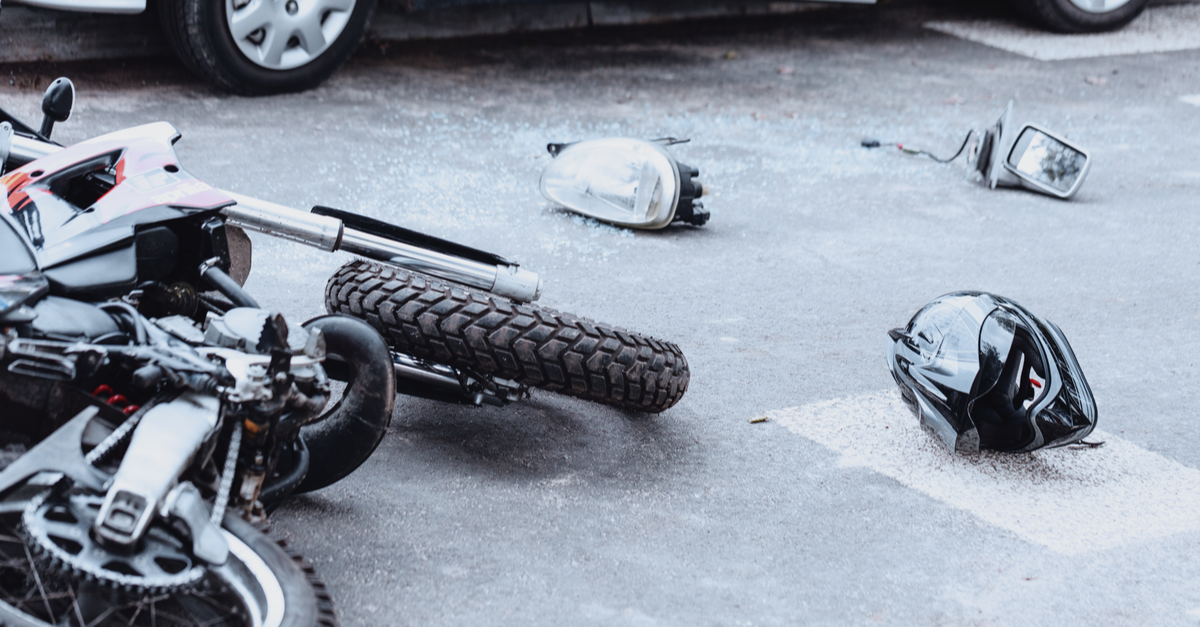 motorcycle accident with a car mirror, headlight, helmet and motorcycle lying