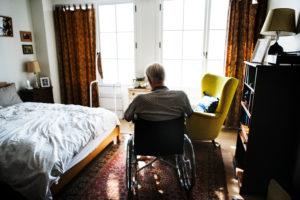 elderly man sitting alone in a New York nursing home room