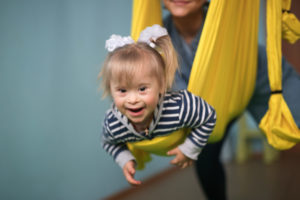 toddler with Cerebral palsy swinging in yellow sling