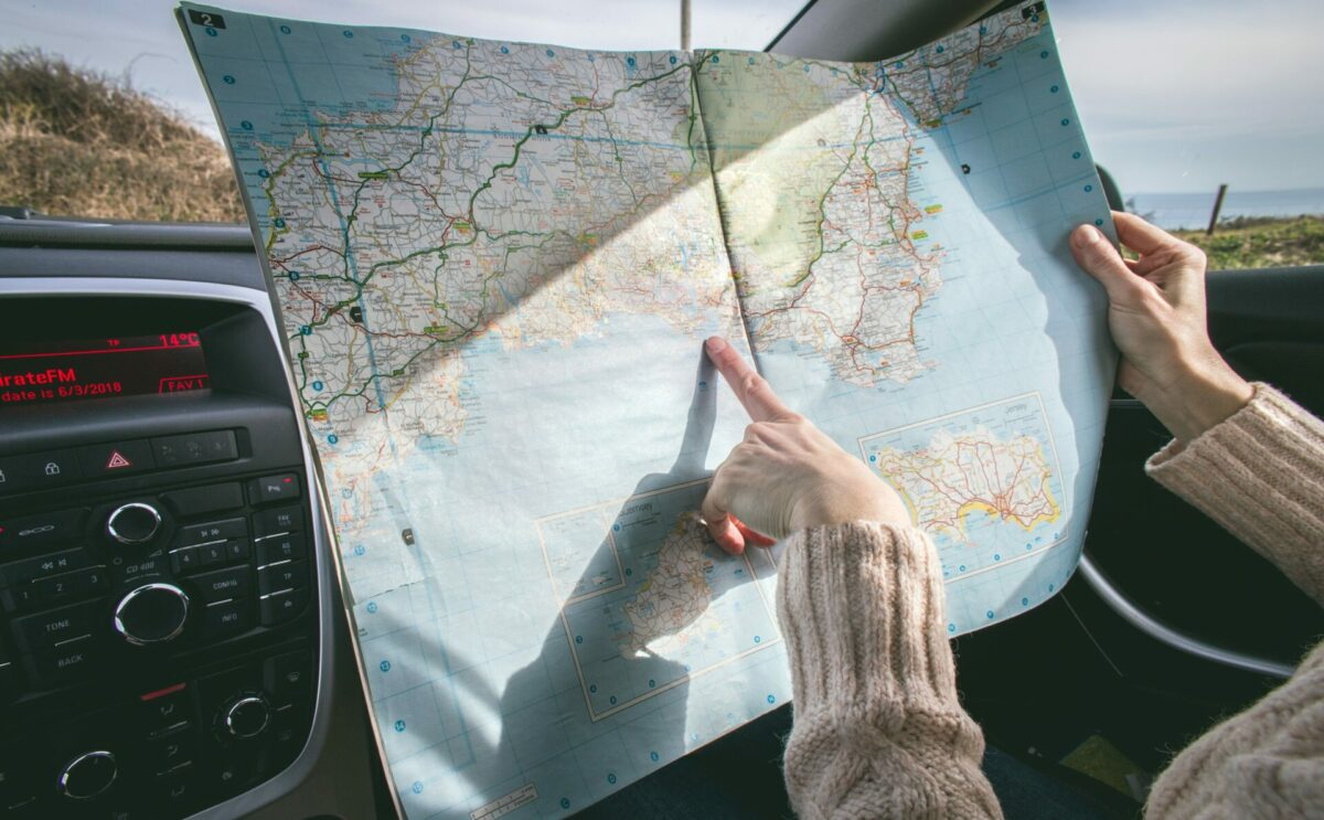 New York woman pointing to road trip destination on map