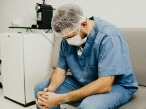 doctor looking down, fatigued after a long shift in NY hospital