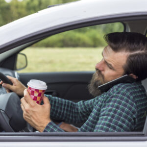 young man drinking and speaking on phone while driving