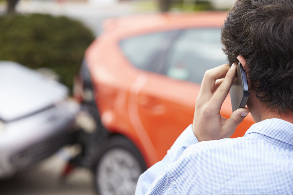 Young person on the phone after car accident