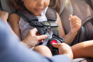 child being buckled into the car seat